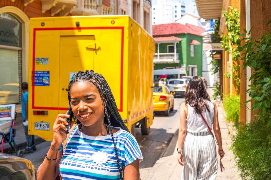 Woman walking down street talking on phone